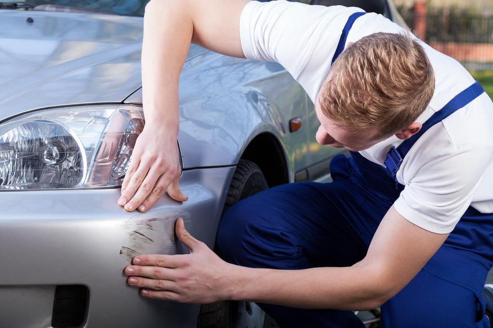 Automonteur bekijkt schade aan auto voor de autoverzekering